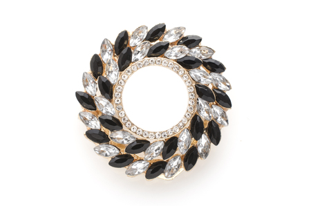 round brooch with gems on a white background