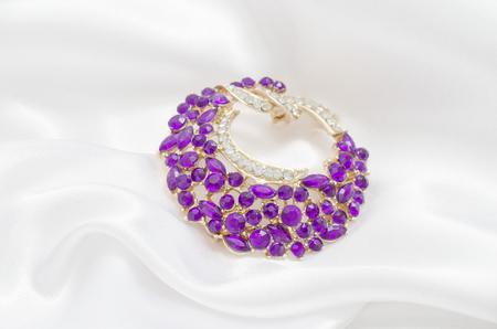 golden round brooch with purple diamonds on white silk