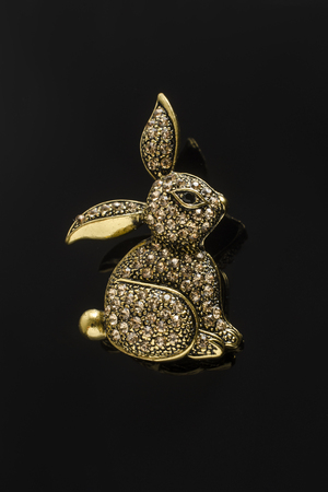 gold brooch bunny with diamonds isolated on black