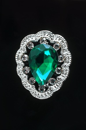 silver brooch drop with green stone isolated on black Stock Photo