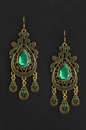 gold earrings with green stones isolated on black Stock Photo