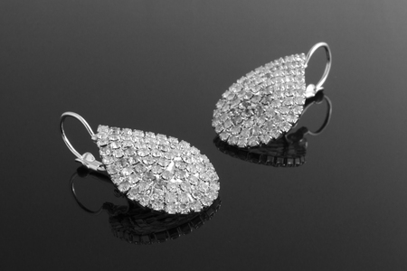 silver earrings with diamonds isolated on black