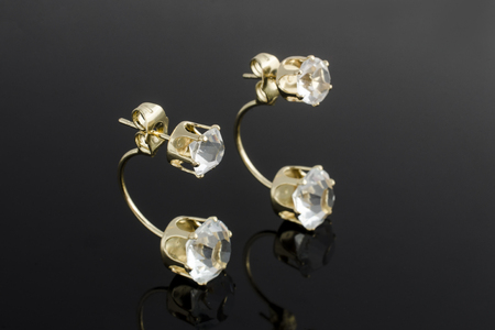 gold earrings with diamonds isolated on black