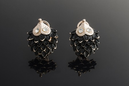 gold earrings hedgehog with diamonds isolated on black