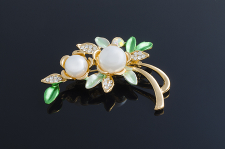 green gemstone: golden brooch flower with pearls isolated on black. brooch flower