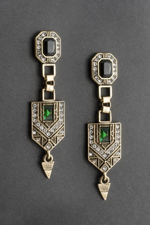 gold earrings in the style of art deco isolated on black