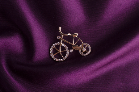 golden brooch bicycle with gems on silk