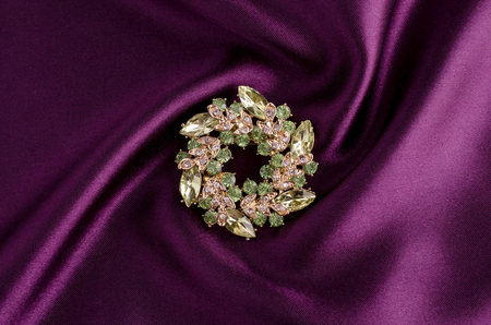 round brooch with gems isolated on a white silk Banque d'images
