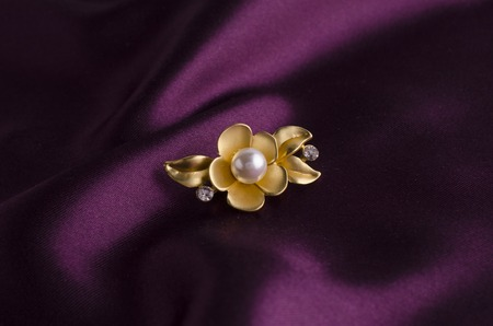 gold brooch flower with pearl on silk