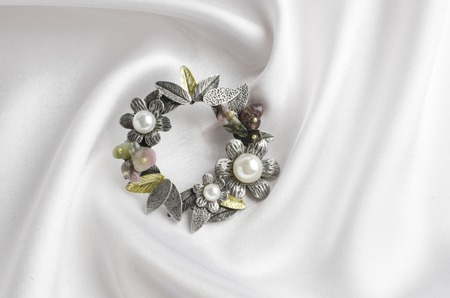 round brooch with flowers and pearls on white silk 스톡 콘텐츠