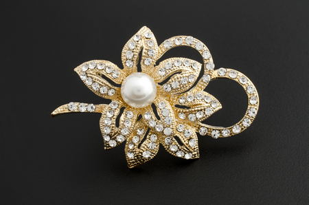 gold brooch flower with pearl isolated on black