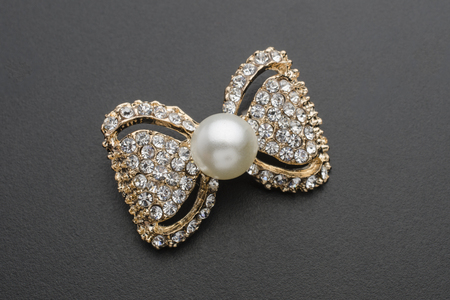 gold brooch bow with pearls and gems isolated on black