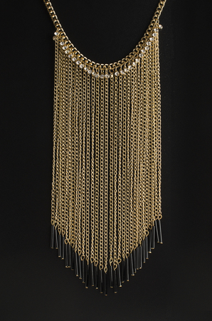 golden necklace with chains and diamonds isolated on black