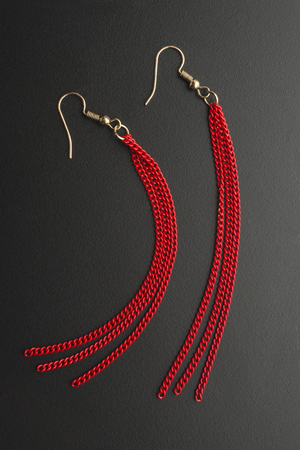 earrings with red chains isolated on black