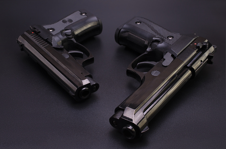 two black automatic pistols on a black background