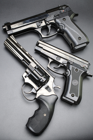 three shiny black pistols on a black background.