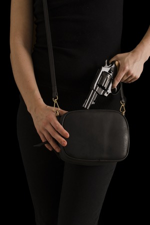 girl hand with a gun on a dark background