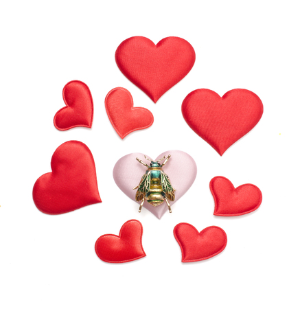 composition brooch bee among hearts isolated on white