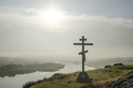 Orthodox cross on the river bank in the rays of the sun
