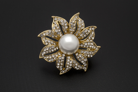 gold brooch flower with a pearl and gems isolated on black