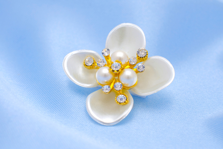 Brooch flower with pearls isolated on silk