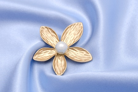 golden brooch flower with pearl isolated on silk Banque d'images