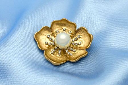 gold brooch flower with a pearl and gems isolated on silk