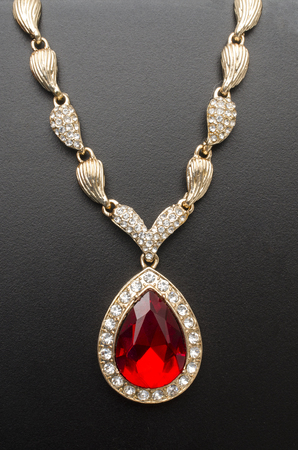 golden pendant with ruby and diamonds isolated on black