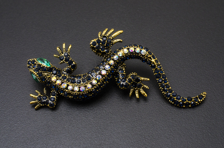 gold brooch lizard with gems isolated on black