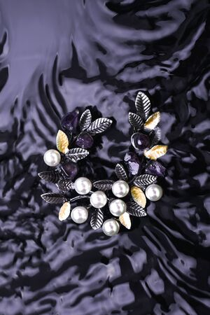 silver brooch twig with pearls and natural stones in the water Standard-Bild