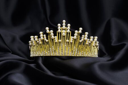 golden crown with pearls and diamonds isolated on black silk