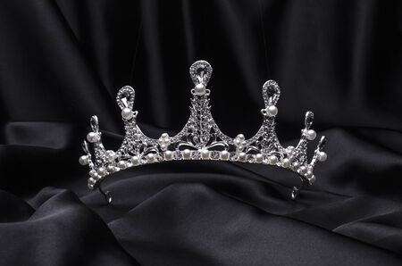 tiara with pearls isolated on a black silk
