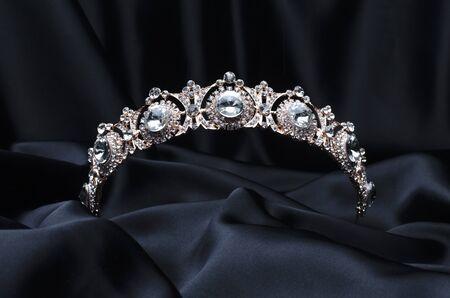 golden tiara with diamonds on a black silk Stock Photo