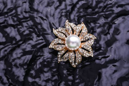 gold brooch flower with a pearl and gems in the water 版權商用圖片