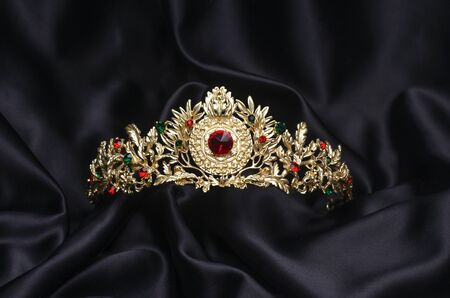 golden crown with rubies  on a black silk