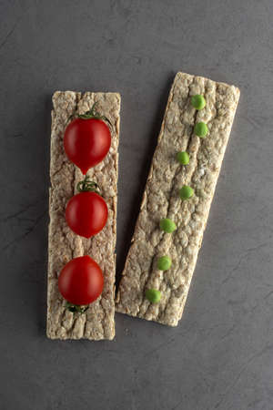 diet food, crispbreads with fresh tomatoes and green peas Standard-Bild