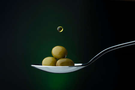 green olives on a spoon on a dark background, a drop of olive oil