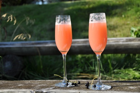 slight: Two glasses with peach colour drink at nature