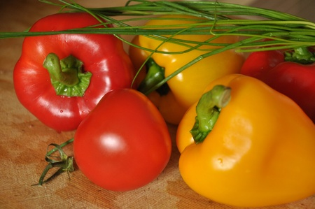 viable: Red and yellow paprika, tomato and green onion on wood surface. Stock Photo