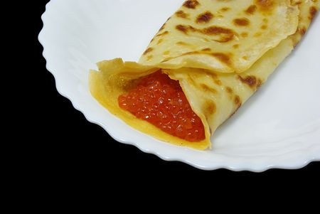 Traditional russian festal day delicacy pancake with caviar isolated on black background photo