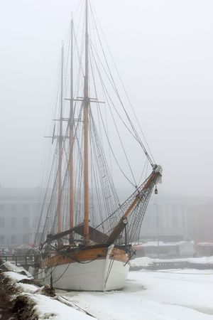 Old sailboat in foggy spring morning by pier photo