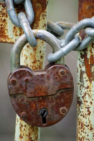 Old closed padlock on the rusty iron gate photo