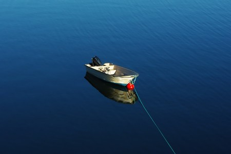 Single boat floating on the calm sea surface Stock Photo - 7607526