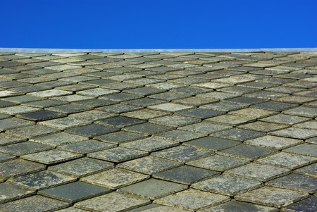 Roof made of plates of slate on blue sky photo