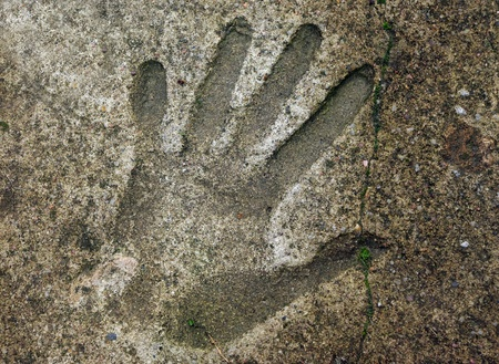 impression: Human handprint in old weathered concrete floor