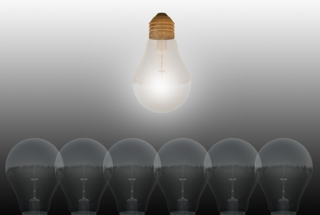 One glowing bulb which illustrates  standing out from the others Stock Photo - 19866356
