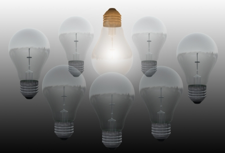 One glowing bulb which illustrates  standing out from the others  Stock Photo - 19866358