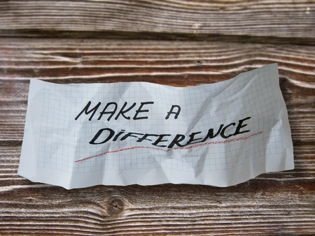 word make a difference   on torn paper on wood background Stock Photo