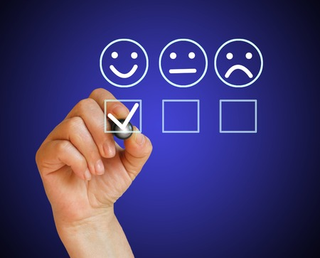 Hand putting check mark with white  marker on customer service evaluation form Stock Photo