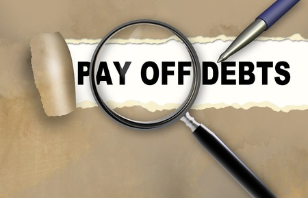Close-up of word PAY OFF DEBTS with pen on it Stock Photo